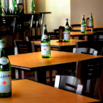 table and chair seating with Pellegrino bottles atop at Canteen Bar and Grill