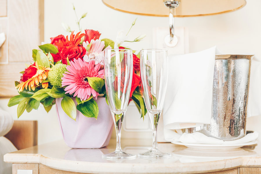 two wine glasses next to a bouquet of flowers in a hotel room